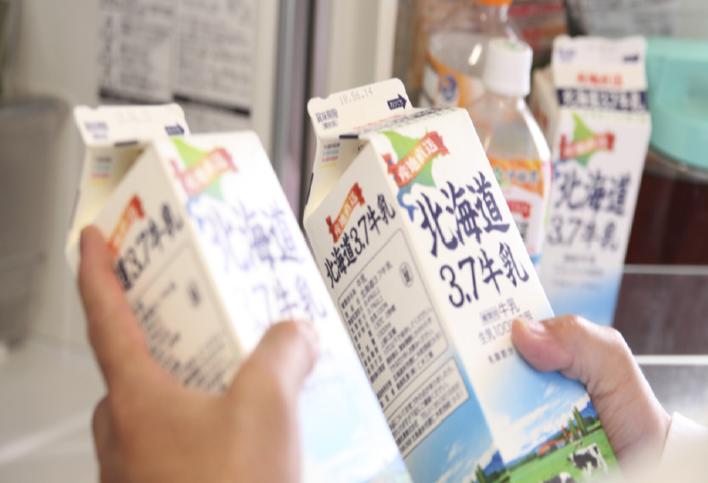冷蔵庫から同じ商品の牛乳パック2 本を手にしている画像