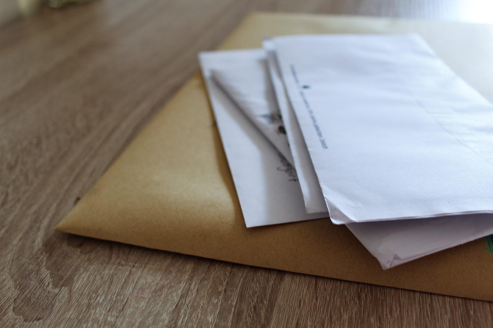 同じ大きさの封筒や郵便物の束の画像